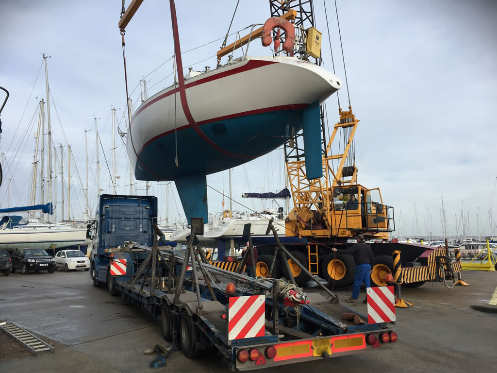 Boat Salvage - A Yacht being lifted onto a boat transport vehicle.