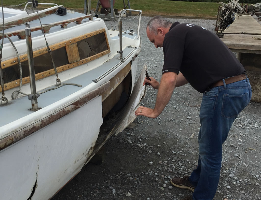 Boat Salvage - An Old Yacht being inspected for damage